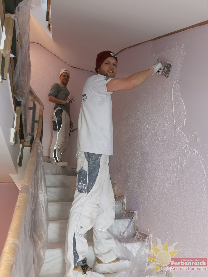 Kratzputz, im Farbton Flieder, Treppengeländer in Sandstrahloptik beschichtet,  stimmige Optik zu den sonst so oft tristen,  vernachlässigten Treppenhäusern.
